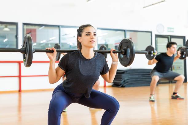 cliente mujer haciendo ejercicio con barra en el club de salud - agacharse fotografías e imágenes de stock