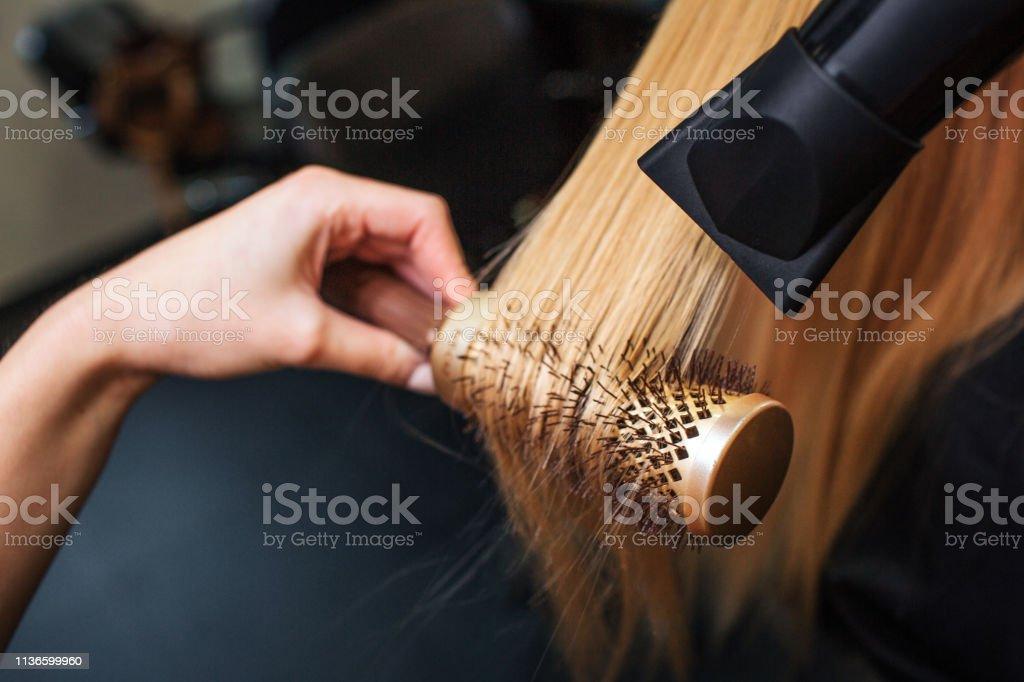 美容院的女客戶。特寫鏡頭的理髮師手烘乾金髮與吹風機和圓形刷子, 做新的髮型 - 免版稅乾的圖庫照片