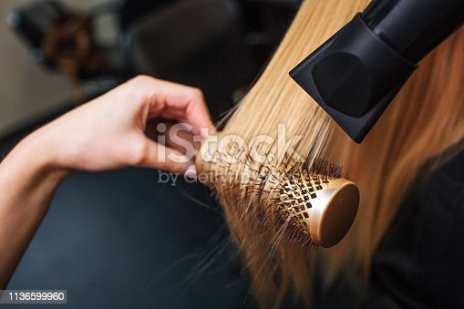 Female client in beauty salon. Close-up of hairdressers hand drying blond hair with hair dryer and round brush, doing professional hairstyle