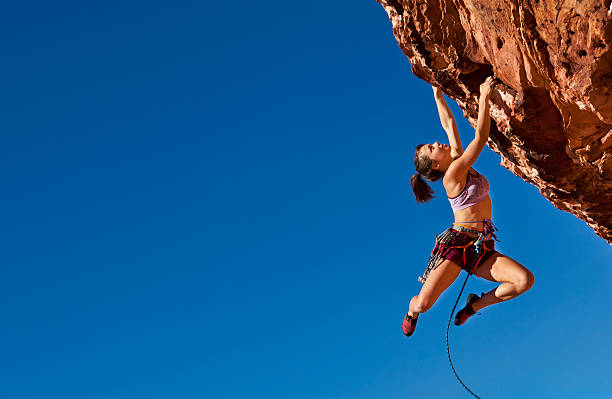 female climber clinging to a cliff. - rock climbing stock photos and pictures