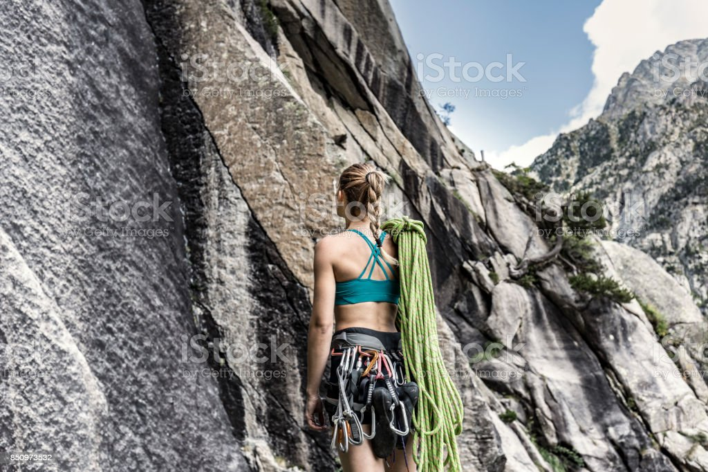 Female climber looking up at the mountain stock photo