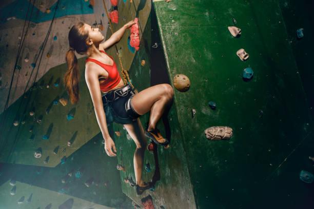 female climber purposeful climbs up the indoor climbing wall - setubal imagens e fotografias de stock