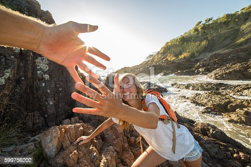 istock Female climbs on cliff, partner pulls out hand for assistance 599756202