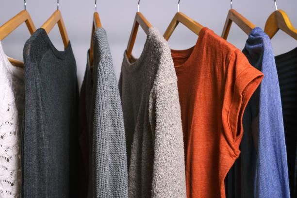 colgando en un estante de la ropa en un armario de tienda o casa de ropa femenina - vestimenta fotografías e imágenes de stock