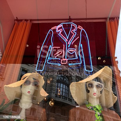 Buenos Aires, Argentina - January 8, 2019: Two mannequins with hats in female clothing store window with a neon light shaping a jacket. The stores in the fancy downtown area of the city go to great lengths to catch clients