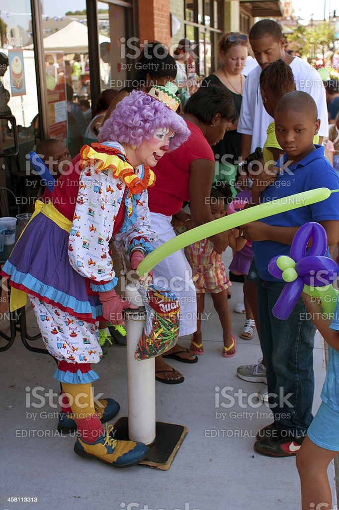 Female Clown Inflates Balloon For Kid At Outdoor Festival royalty-free stock photo