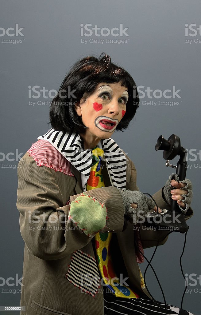 Female Clown With Antique Phone stock photo