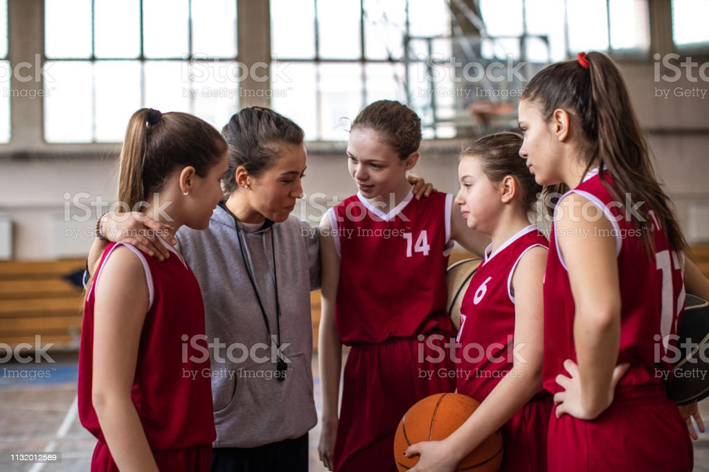 Young female coach talking with teenage girls at basketball court