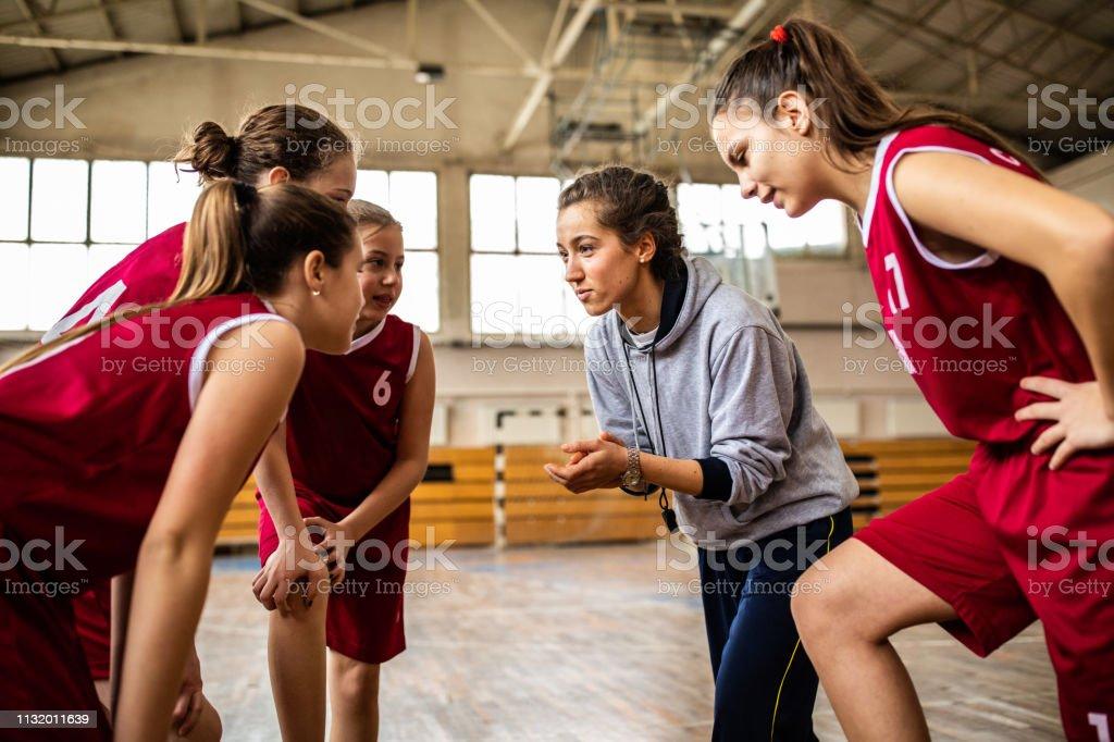 Beautiful female basketball coach cheering young girls to win next...