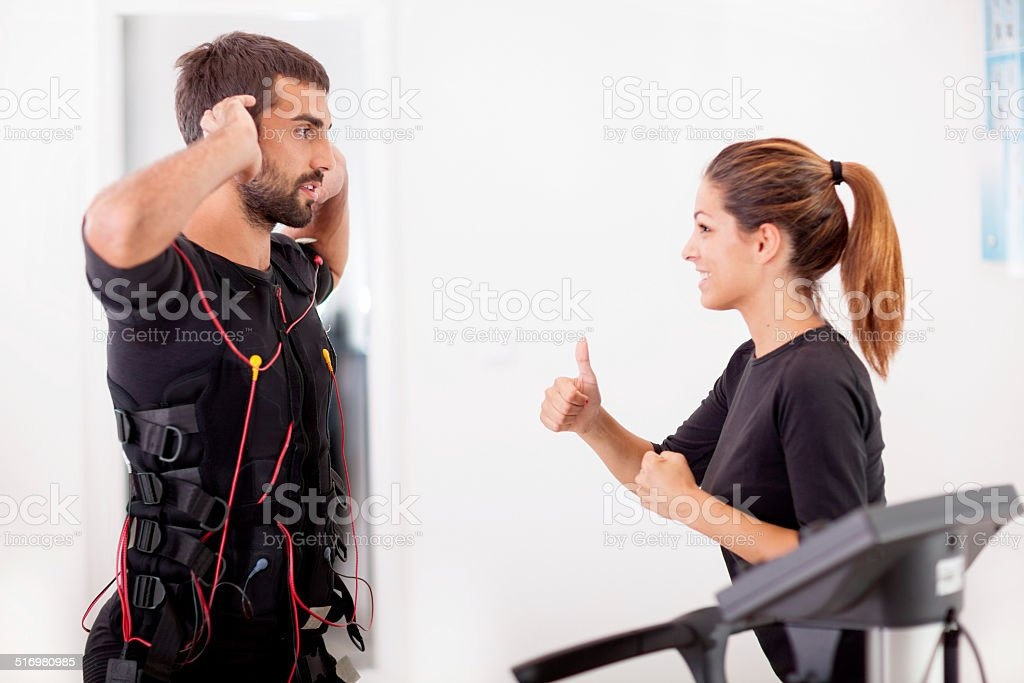 Female coach giving man ems electro muscular stimulation exerci stock photo