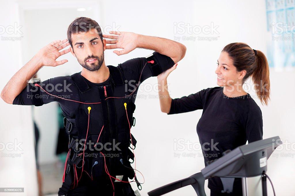 Female coach giving man ems electro muscular stimulation exerci stock photo