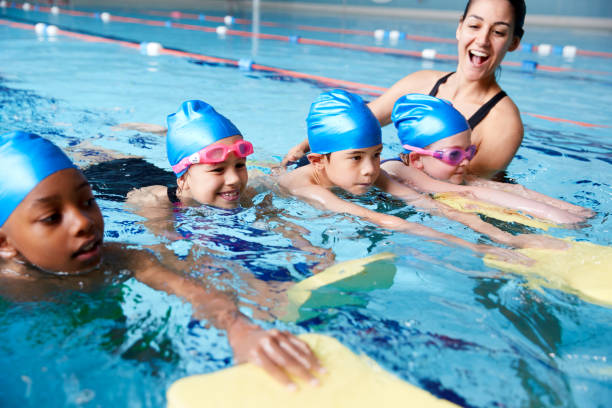 Female Coach In Water Giving Group Of Children Swimming Lesson In Indoor Pool Female Coach In Water Giving Group Of Children Swimming Lesson In Indoor Pool swimming stock pictures, royalty-free photos & images