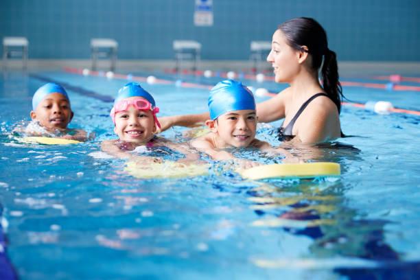 Weibliche Trainerin in Wasser geben Gruppe von Kindern Schwimmstunde im Hallenbad – Foto