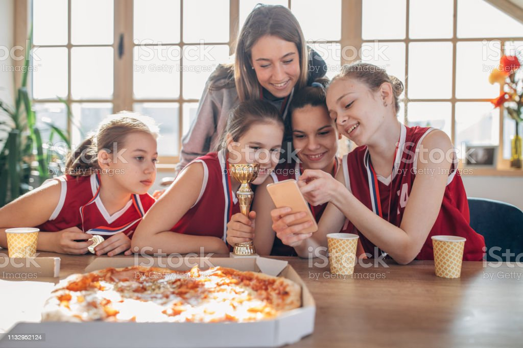 Female coach making selfie with basketball team while celebrating...