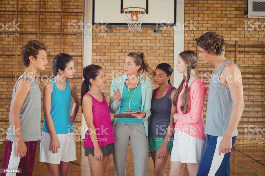 Female coach mentoring high school kids in basketball court