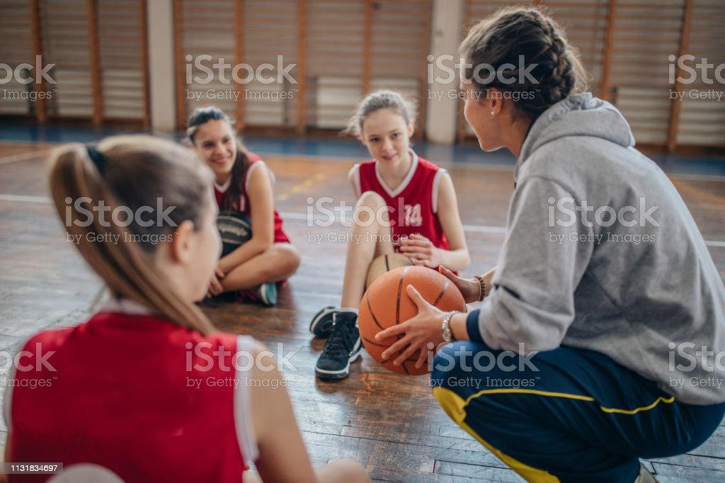 Female coach sitting with basketball team on basketball court