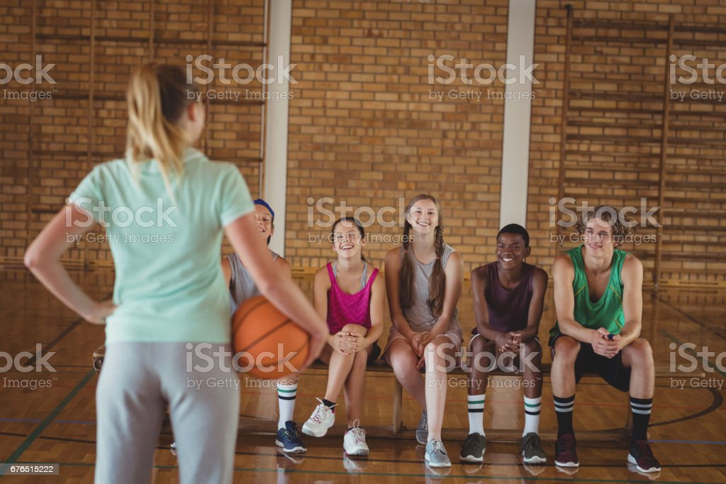Rear view of female coach standing with basketball in basketball court
