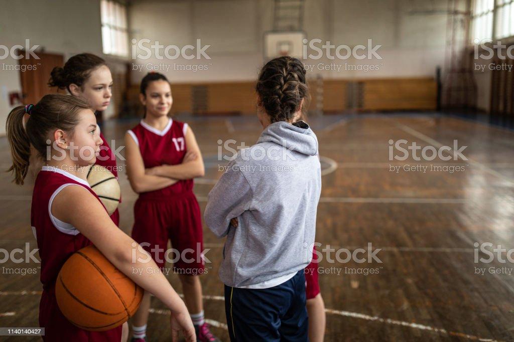Group of teenage girls listening female basketball coach while...