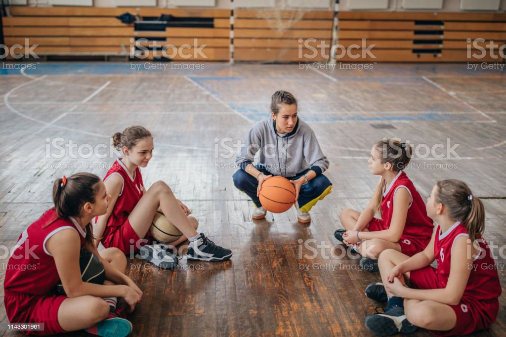 Female coach with basketball team on basketball court