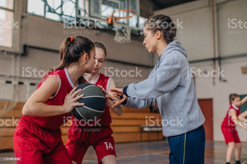 Female coach practicing with basketball team on basketball court
