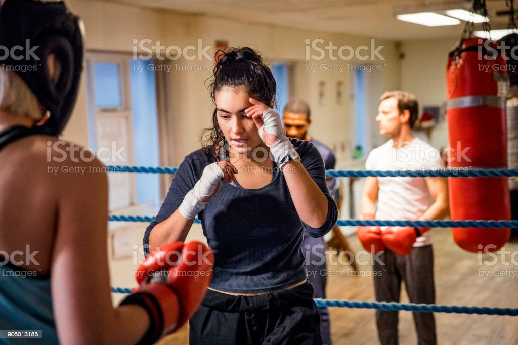 A woman in a boxing ring coaching another woman wearing protective...