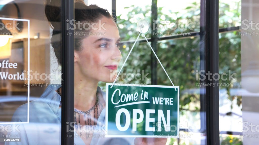 Female coffee shop owner opening the shop - Photo