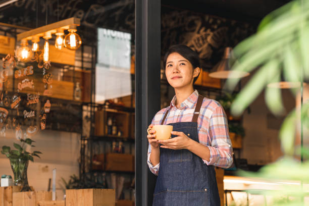 Female coffee shop owner standing confidently in front of her cafe A female entrepreneur standing in front of her new business, a small coffee shop in Taipei. She is holding a cup of coffee, looking off into the distance. tea room stock pictures, royalty-free photos & images