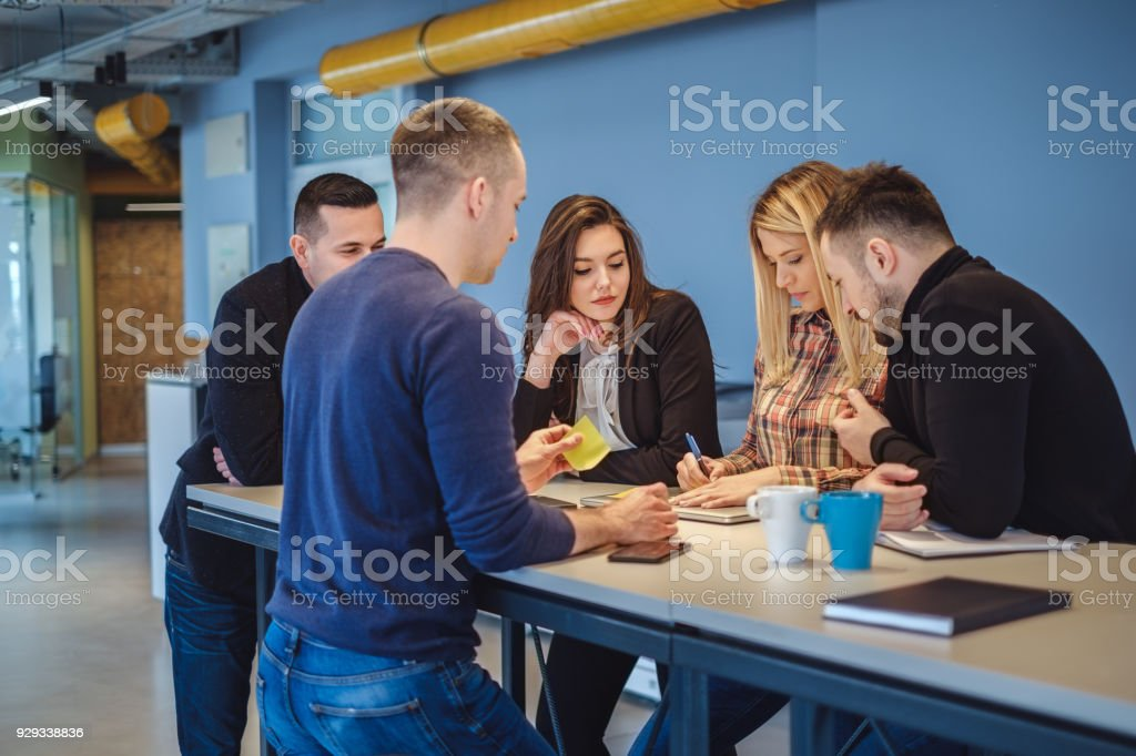 Female colleague writhing on a paper while everybody watching her stock photo