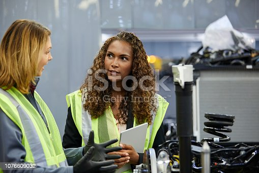 941796726istockphoto Female colleagues discussing over car chassis 1076609032