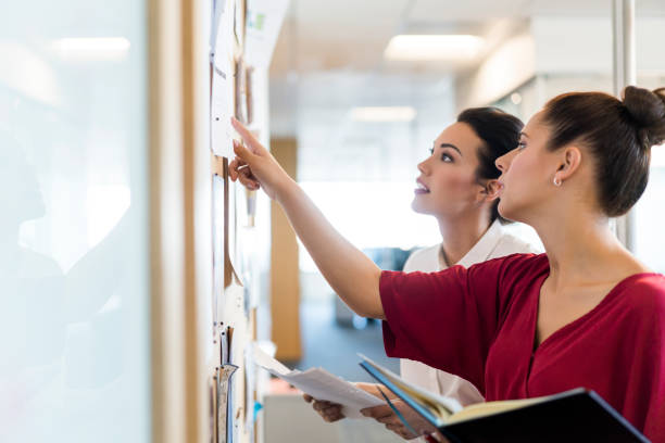female colleagues discussing over notes in office - bulletin board stock pictures, royalty-free photos & images
