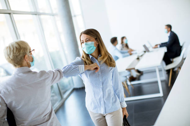 Female colleagues keeping social distance, greeting each other by bumping elbows, preventing covid 19 coronavirus infection spread stock photo