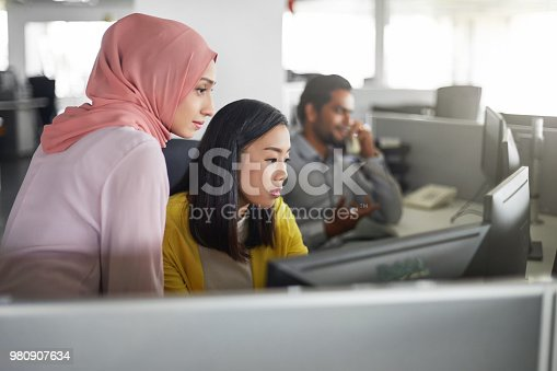 istock Female colleagues working at computer desk 980907634