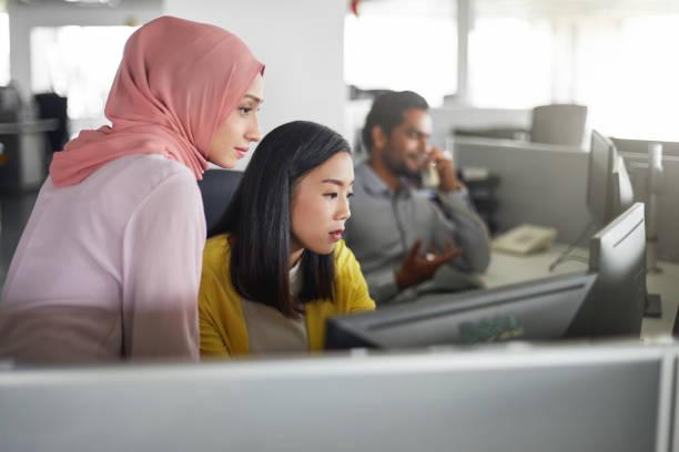 在電腦桌工作的女同事 - 亞洲 個照片及圖片檔