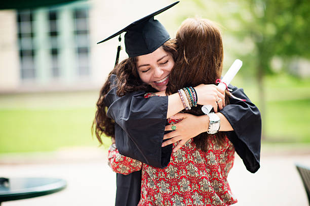Female college graduate Female college student hugging her mother on graduation date immigrant stock pictures, royalty-free photos & images
