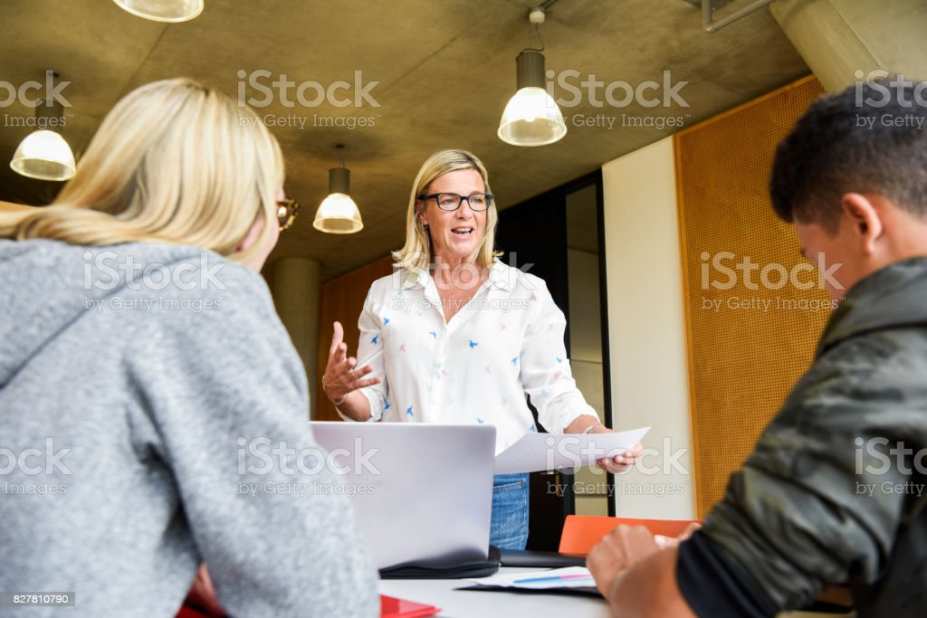 Female college lecturer explaining to young students in classroom Mature woman gesturing and holding paper, male and female college students listening in forground 20-24 Years Stock Photo