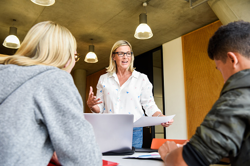 Female College Lecturer Explaining To Young Students In Classroom Stock Photo - Download Image Now