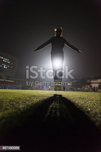 istock female college student jumping up in the soccer field 657460056