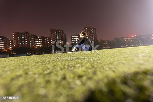 istock female college student playing phone on grass field 657459890