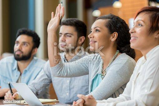 600055398 istock photo Female college student raises hand during class 962641966