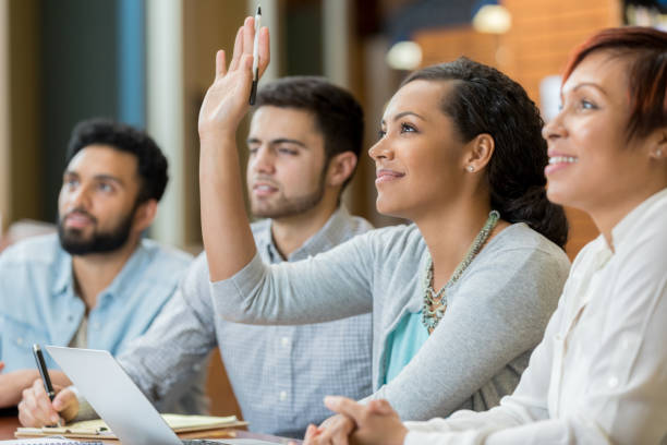 Female college student raises hand during class stock photo