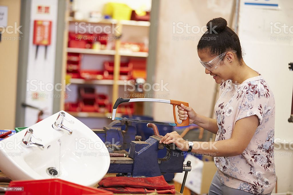 Female College Student Studying Plumbing Working At Bench stock photo