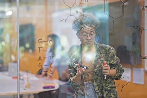 A female african-american college student studies biology on a glass pane. She is holding two markers and has molecules drawn in front of her.