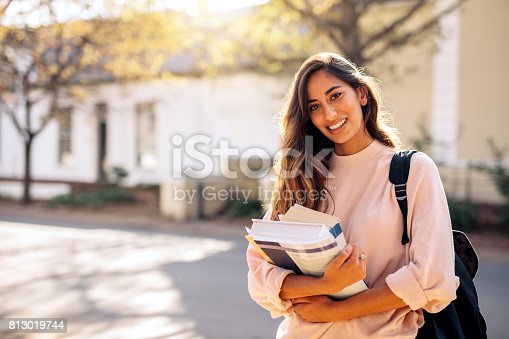 istock Female college student with books outdoors 813019744