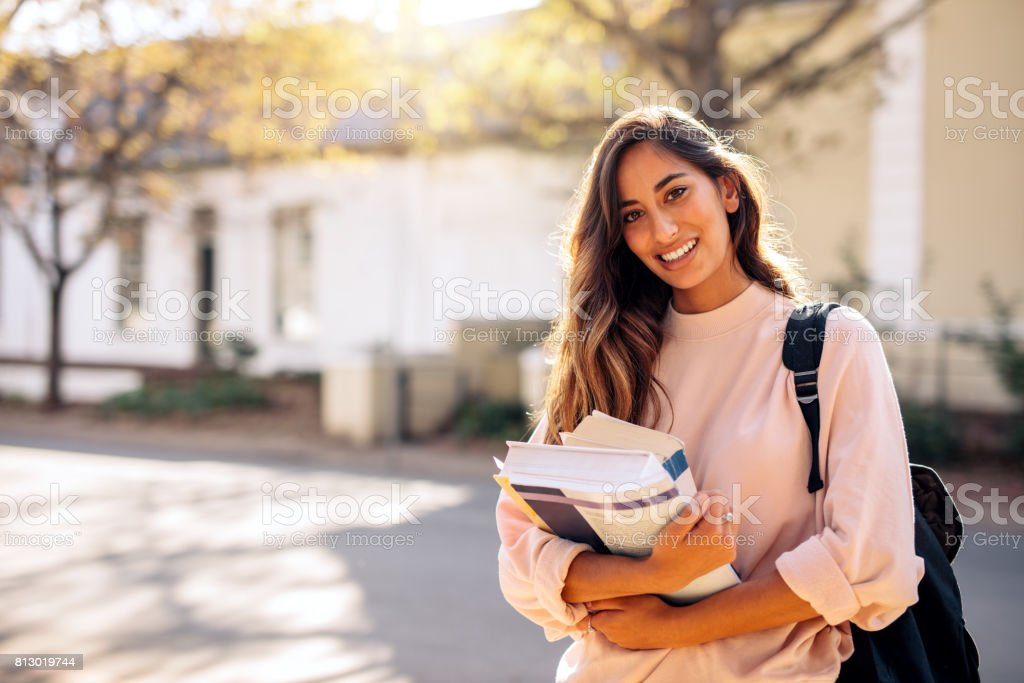 Female college student with books outdoors stock photo