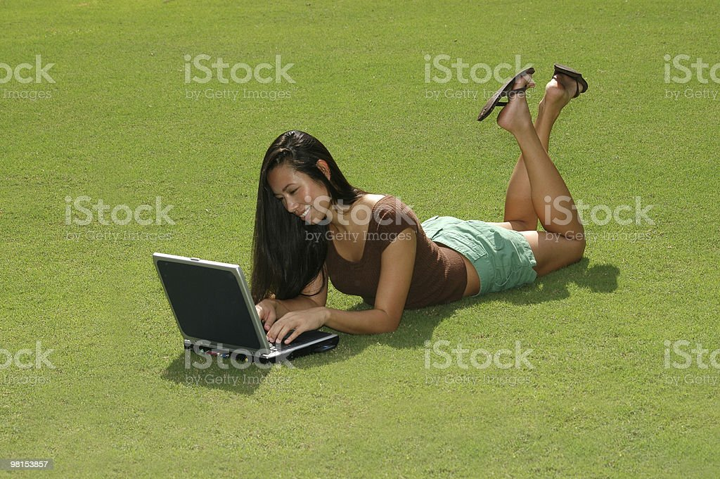 Female College Student with Laptop on Grass Lawn royalty-free stock photo