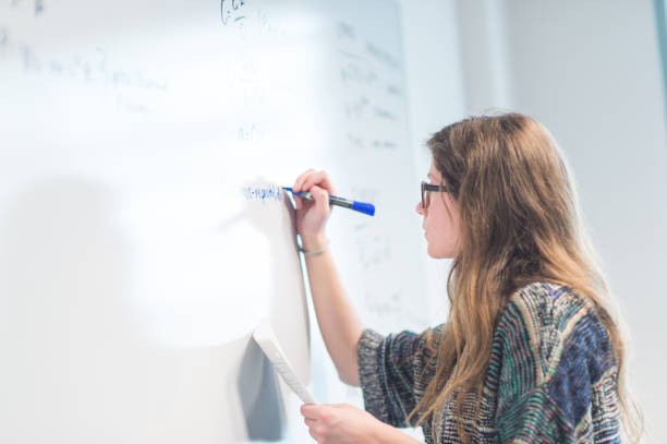 female college student writes out a math equation on whiteboard. - day in the life series stock pictures, royalty-free photos & images