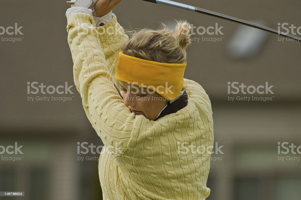 Female collegiate golfer swinging golf club royalty-free stock photo