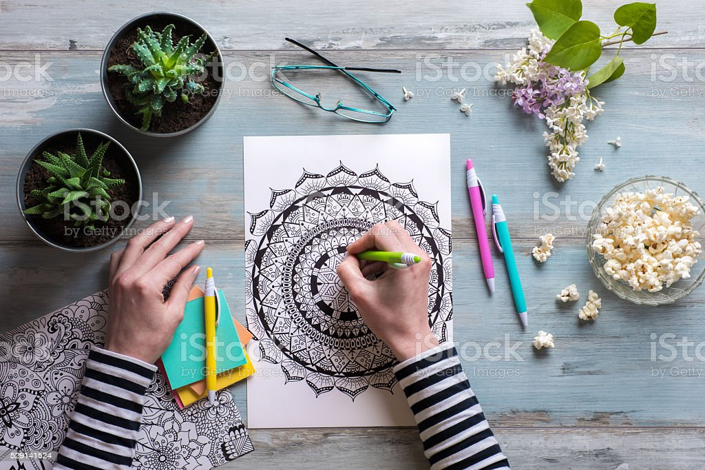 Female coloring adult coloring books, new stress relieving trend stock photo