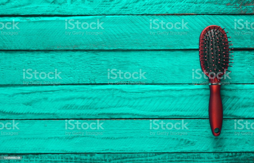 Female comb on a wooden turquoise background. Trend of minimalism. Top view. Copy space. стоковое фото