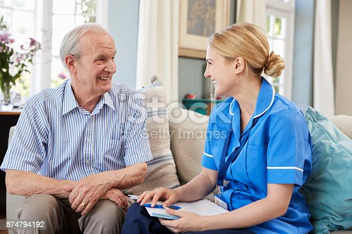 istock Female Community Nurse Visits Senior Man At Home 874794192